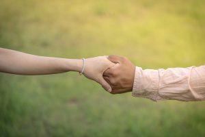 Zwei Menschen, die sich die Hände reichen