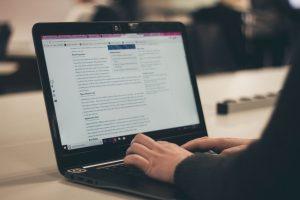 Bild von Frau am Laptop, die einen Text schreibt